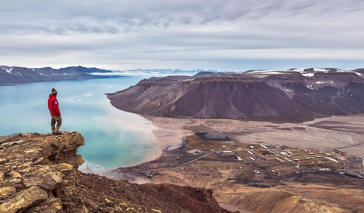 A person on top a cliff looking down on Pyramiden