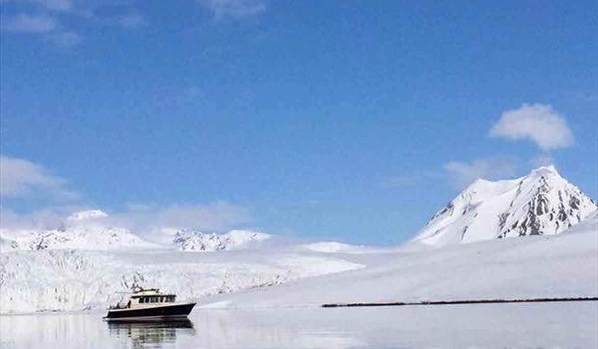 Spitsbergen Express Svalbard- a boat surrounded by majestic mountains