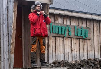 A man standing in front of Tommy's Lodge